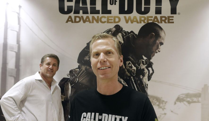 """This July 31, 2014 shows Glen Schofield, left, and Michael Condrey, co-founders of Sledgehammer Games in front of a """"Call of Duty: Advanced Warfare"""" sign in Foster City, Calif. The game is scheduled for release Nov. 4. (AP Photo/Jeff Chiu)"""