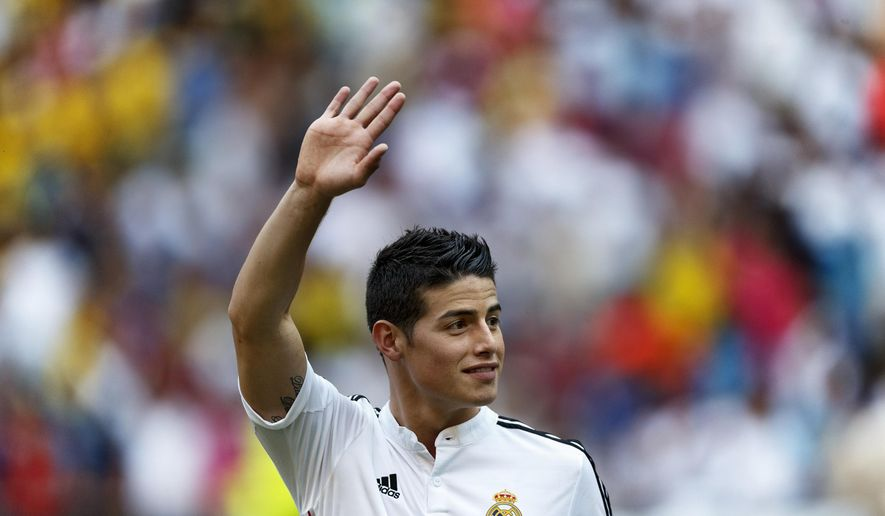 FILE - In this July 22, 2014 file photo, new Real Madrid player James Rodriguez, from Colombia, waves during his official presentation at the Santiago Bernabeu stadium in Madrid, Spain. Real Madrid have signed Rodriguez from Monaco on a six-year contract,  (AP Photo/Daniel Ochoa de Olza, File)