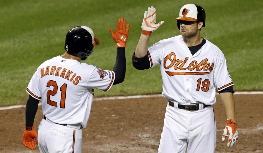 Baltimore Orioles' Chris Davis, right, greets teammate Nick Markakis after batting him in on a home run in the fifth inning of a baseball game against the New York Yankees, Monday, Aug. 11, 2014, in Baltimore. (AP Photo/Patrick Semansky)