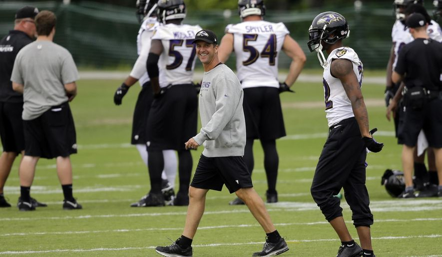 Baltimore Ravens head coach John Harbaugh walks on the field during an NFL football training camp practice, Monday, Aug. 11, 2014, in Owings Mills, Md. (AP Photo/Patrick Semansky)