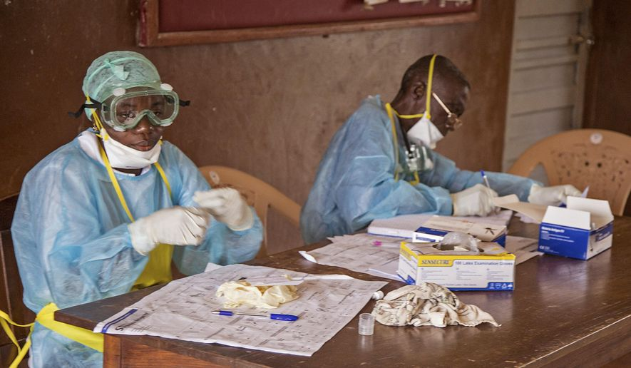 In this photo taken Saturday, Aug. 9, 2014,  health worker wearing protective clothing and equipment, out of fear for the  deadly Ebola virus, sit at a desk at the Kenema Government Hospital situated in the Eastern Province in Kenema, 300 kilometers, (186 miles) from the capital city of Freetown, Sierra Leone.  Over the decades, Ebola cases have been confirmed in 10 African countries, including Congo where the disease was first reported in 1976. But until this year, Ebola had never come to West Africa.  (AP Photo/ Michael Duff)
