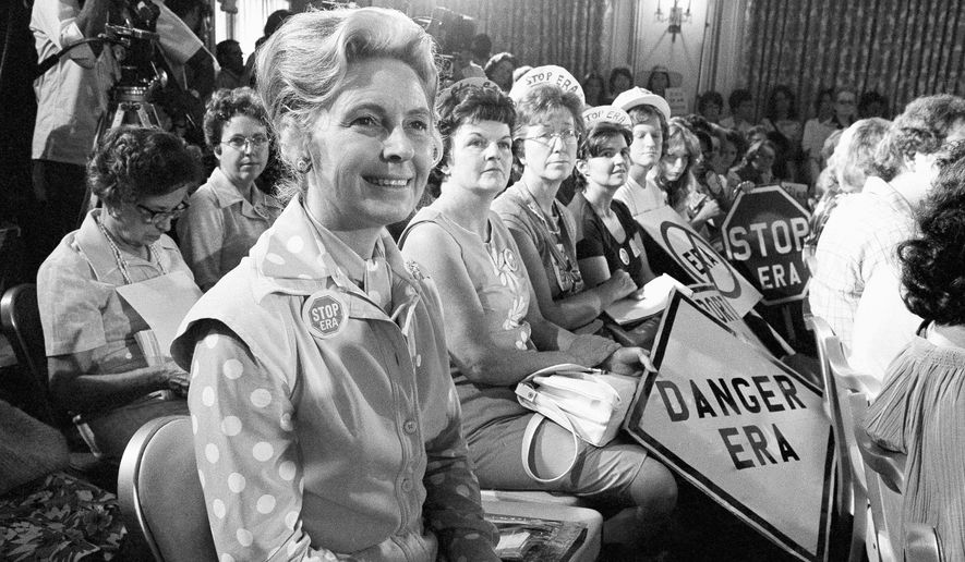 FILE - In this Aug. 10, 1976, file photo, women opposed to the Equal Rights Amendment sit with Phyllis Schlafly, left, national chairman of Stop ERA, at hearing of Republican platform subcommittee on human rights and responsibilities in a free society in Kansas City, Mo. One of the leading opponents of the ERA during the 1970s was conservative Illinois lawyer Phyllis Schlafly, who launched a campaign called Stop ERA and is credited with helping mobilize public opinion against the amendment in some of the states that balked at ratifying it. (AP Photo/File)