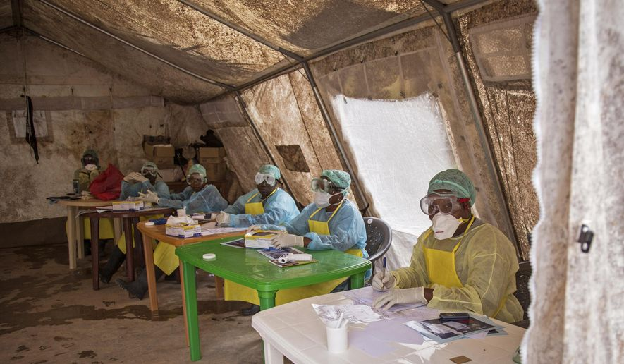 In this photo taken Saturday, Aug. 9, 2014,  a health worker wearing protective clothing and equipment, await patients to screen against the deadly Ebola virus at the Kenema Government Hospital situated in the Eastern Province in Kenema, 300 kilometers, (186 miles) from the capital city of Freetown, Sierra Leone.  Over the decades, Ebola cases have been confirmed in 10 African countries, including Congo where the disease was first reported in 1976. But until this year, Ebola had never come to West Africa.  (AP Photo/ Michael Duff)