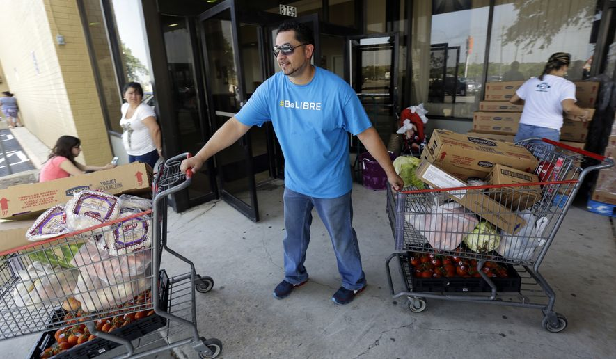 ** FILE ** In this July 3, 2014, photo, pastor Marcus Burgos, center, helps distribute groceries at a food bank at the Abundant Life Church in San Antonio. The food bank is cosponsored by the Libre Initiative, partly funded by conservative billionaires Charles and David Koch, which is looking to make inroads with the rising voting block of Hispanics. (AP Photo/Eric Gay)