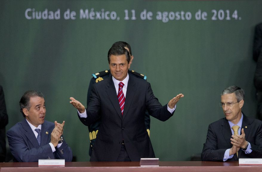 Mexican President Enrique Pena Nieto, center, is applauded by Senate leader Raul Cervantes Andrade, left, and House Speaker Jose Gonzalez Morfin at a ceremony to mark the signing of a historic energy reform bill, at the National Palace in Mexico City, Monday, Aug. 11, 2014. The law will open the state-run oil, gas and electricity industries to foreign and private companies. Mexico is hoping for tens of billions of dollars in outside investment in deep-water oil drilling and shale gas production. (AP Photo/Rebecca Blackwell)