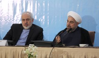 "In this photo released by the official website of the office of the Iranian Presidency, Iran's President Hassan Rouhani, right, speaks during an annual meeting of Iranian ambassadors as Foreign Minister Mohammad Javad Zarif listens, in Tehran, Iran, Monday, Aug. 11, 2014. Rouhani has offered his harshest criticism yet of hard-liners opposed to making a deal over its contested nuclear program with world powers, saying they should go ""to hell."" (AP Photo/Mohammad Berno, Iranian Presidency Office)"