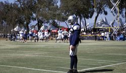 Dallas Cowboys cornerback Orlando Scandrick stands on the field during a football practice with the Oakland Raiders on Tuesday, Aug. 12, 2014, in Oxnard, Calif. Scandrick has apologized to his family, teammates and organization for failing a drug test that will force him to be suspended for the first four games of the season. The NFL announced the suspension on Tuesday. (AP Photo/Jae C. Hong)