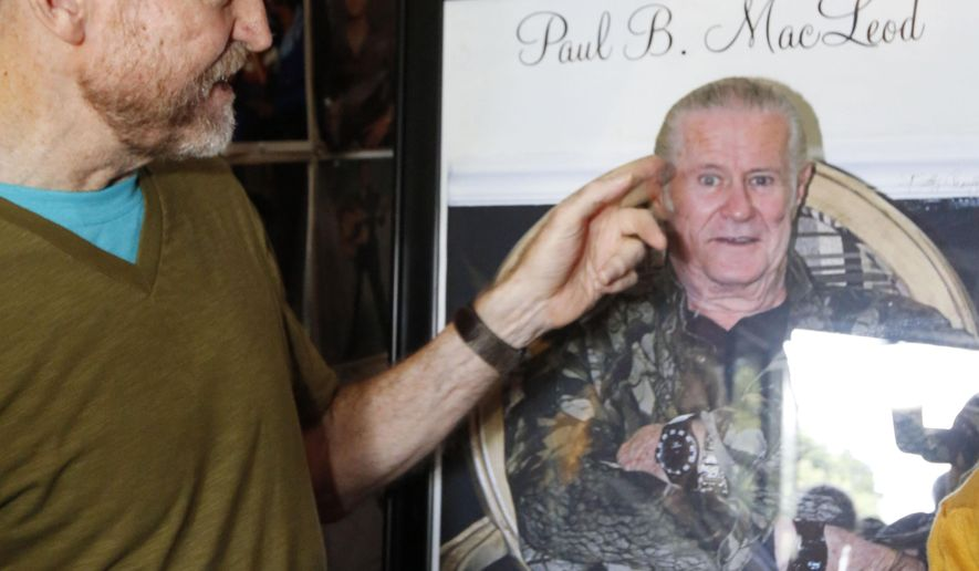 Vernon Chadwick of Oxford, points out the haircut of the late Paul MacLeod, an Elvis-obsessed man who turned his eclectic collection of photos, records, albums and knick-knacks into a museum at his antebellum home named Graceland Too, honoring Presley, Tuesday, Aug. 12, 2014 in Holly Springs, Miss. Several of MacLeod's friends gave tours to visitors at the museum-home. MacLeod's memorial takes place the week that fans commemorate the anniversary of Presley's death on Aug. 16, 1977 at his Graceland mansion in Memphis. (AP Photo/Rogelio V. Solis)