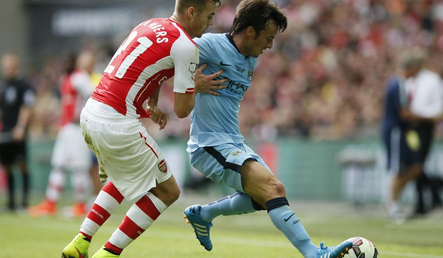 Arsenal's Calum Chambers, left,  challenges Manchester City's David Silva during the English FA Community Shield soccer match at Wembley Stadium, London Sunday, Aug. 10, 2014. (AP Photo/Alastair Grant)