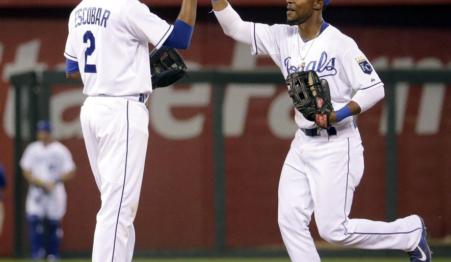 Kansas City Royals' Alcides Escobar, left, and Jarrod Dyson celebrate after their baseball game against the Oakland Athletics, Monday, Aug. 11, 2014, in Kansas City, Mo. The Royals won 3-2. (AP Photo/Charlie Riedel)