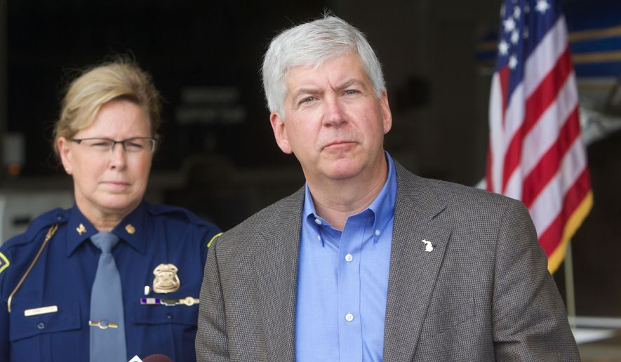 Michigan Gov. Rick Snyder addresses reporters at the Lansing, Mich., airport, Tuesday, Aug. 12, 2014, before flying out to survey the severe flooding in the Detroit area. Snyder told reporters that he'll have a better idea of the scope of the damage after the flyover. Snyder cut short a trip to the Upper Peninsula to survey the damage, after more than 5 inches of rain fell within a few hours across parts of southeastern Michigan, leaving streets and freeways impassable. (AP Photo/Grand Rapids Press, Fritz Klug)