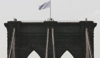 In this July 22, 2014, file photo, New York City police officers stand at the base of a white flag flying atop the west tower of the Brooklyn Bridge. (AP Photo/Richard Drew, File)