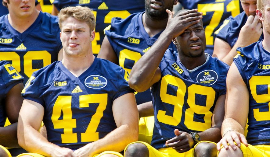 Michigan linebacker Jake Ryan (47), quarterback Devin Gardner (98) and teammates sit for a photo during the NCAA college football team's preseason media day, Sunday, Aug. 10, 2014, at Michigan Stadium in Ann Arbor, Mich. (AP Photo/Tony Ding)