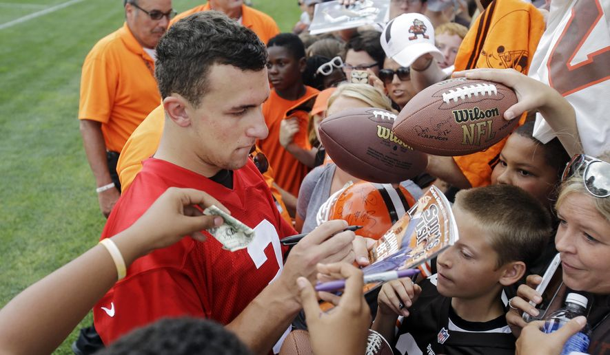Cleveland Browns quarterback Johnny Manziel signs for fans after practice at NFL football training camp in Berea, Ohio Tuesday, Aug. 12, 2014. (AP Photo/Mark Duncan)