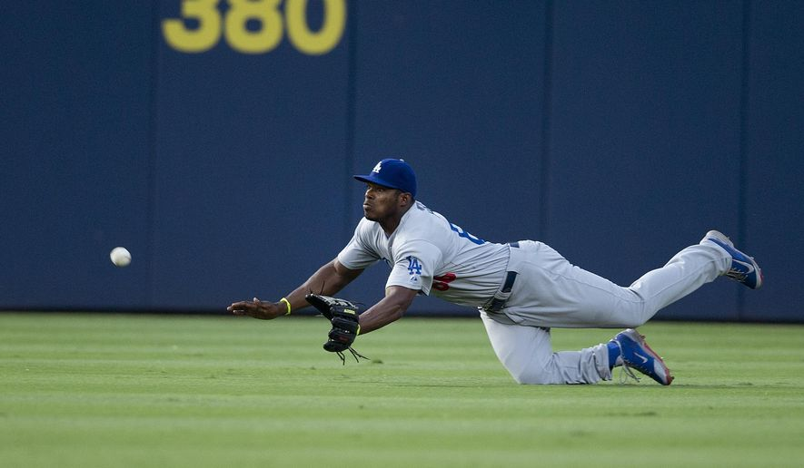 Los Angeles Dodgers center fielder Yasiel Puig makes a diving attempt for a ball hit for an RBI-double by Atlanta Braves' Justin Upton in the third inning of a baseball game Tuesday, Aug. 12, 2014, in Atlanta. (AP Photo/John Bazemore)