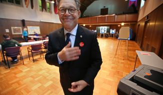 "Sen. Al Franken, D-Minn., places his ""I voted"" sticker on his suit coat after he voted at Westminster Presbyterian Church in downtown Minneapolis, Tuesday, Aug. 12, 2014. (AP Photo/Star Tribune, Elizabeth Flores)"