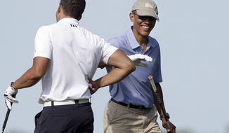 President Barack Obama, right, smiles as he gives a pat on the arm to Cyrus Walker, left, cousin of White House senior adviser Valerie Jarrett, while golfing at Vineyard Golf Club, Tuesday, Aug. 12, 2014, in Edgartown, Mass., on the island of Martha's Vineyard. President Obama is taking a two-week summer vacation on the island. (AP Photo/Steven Senne)