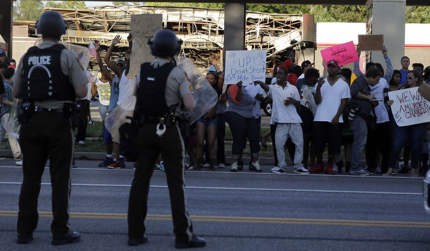 Protesters yell at police Tuesday, Aug. 12, 2014, in Ferguson, Mo. The Rev. Al Sharpton pressed police Tuesday to release the name of the officer who fatally shot an unarmed teenager in suburban St. Louis, and he pleaded for calm after two nights of violent protests over the young man's death. (AP Photo/Jeff Roberson)