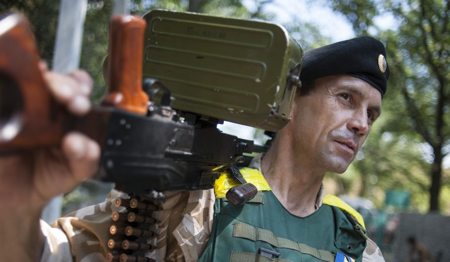 """A Ukrainian government soldier from the """"Donbass"""" battalion guards a position in the village of Mariinka, near Donetsk, eastern Ukraine, Tuesday, Aug. 12, 2014. Kiev and the West have repeatedly opposed any Russian humanitarian aid mission to eastern Ukraine, fearing that such a move could preface an intervention by Moscow. Throughout the conflict, Ukraine and the West have accused Russia of aiding the rebels with arms and expertise, a charge that the Kremlin has denied. (AP Photo/Evgeniy Maloletka)"""