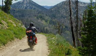 This photo taken on July 20, 2014, shows a motorcycle rider on a backcountry road heading to Graham, about 45 miles northeast of Idaho City, Idaho. Getting to Graham means going through a long gravel road and over an 8,300-foot pass before descending into the headwaters of the North Fork of the Boise River.  (AP Photo/The Idaho Statesman, Roger Phillips)  LOCAL TELEVISION OUT (KTVB 7); MANDATORY CREDIT
