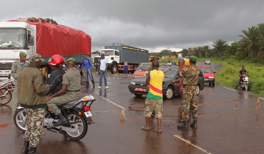 In this photo taken on Tuesday, Aug. 12,  2014,  Guinea soldiers stand around a  rope across the road that separates Guinea and Sierra Leone, and works as a makeshift border control checkpoint at  Gbalamuya-Pamelap, Guinea. As Guinea closed its border with Sierra Leone at the weekend in an attempt to halt the spread of the deadly Ebola virus, people and goods were not able to cross to either side.  (AP Photo/ Youssouf Bah)
