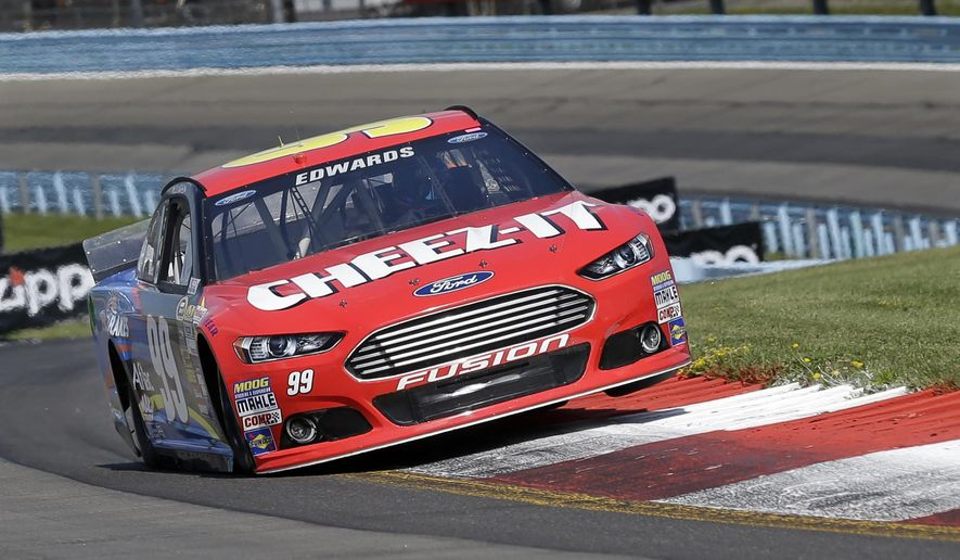 Carl Edwards (99) hits a curb as he drives through the esses during a qualifying session for Sunday's NASCAR Sprint Cup Series auto race at Watkins Glen International, Saturday, Aug. 9, 2014, in Watkins Glen N.Y. (AP Photo/Mel Evans)