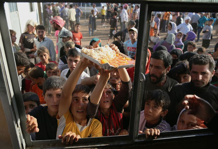 desperation: Displaced Yazidi Iraqis gather for food at the Nowruz camp in Derike, Syria. While the U.S. and Iraqi militaries have given food and water, the Kurds took it on themselves to rescue them, a sign of how Syria's Kurds are using the conflict to establish their own rule. (Associated Press)