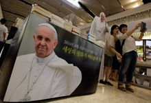 POPULAR: Visitors take souvenir photos by pictures of Pope Francis at a bookstore in Seoul. During a five-day trip to South Korea, the pope will preside over a beatification ceremony for 124 Korean martyrs. (Associated Press)