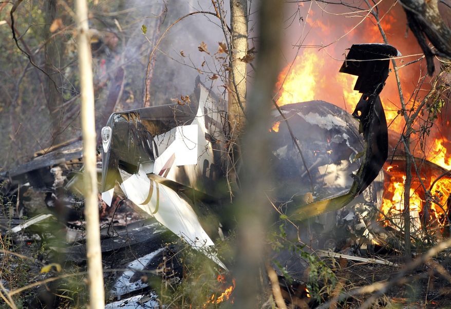 FILE - In this Nov. 10, 2013, file photo, a small plane piloted by Dr. Perry Inhofe, the son of Oklahoma Sen. Jim Inhofe, burns after crashing near a residential area in Owasso, Okla. Perry Inhofe was flying a new type of aircraft for the first time alone when he was killed last November in the plane crash, according to a factual report released this week by the National Transportation Safety Board. (AP Photo/Tulsa World, Mike Simons, File)