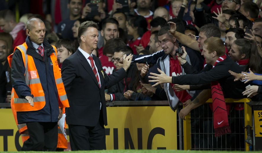 Manchester United's new manager Louis van Gaal, second left, shakes hands with supporters as he walks down th touchline after his team's pre season friendly soccer match against Valencia at Old Trafford Stadium, Manchester, England, Tuesday Aug. 12, 2014. Manchester United won the game 2-1 with a late winner from Marouane Fellaini. (AP Photo/Jon Super)