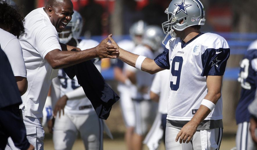 Los Angeles Dodgers part-owner Magic Johnson, left, and Dallas Cowboys quarterback Tony Romo shake hands before the team's joint football practice with the Oakland Raiders on Tuesday, Aug. 12, 2014, in Oxnard, Calif. (AP Photo/Jae C. Hong)