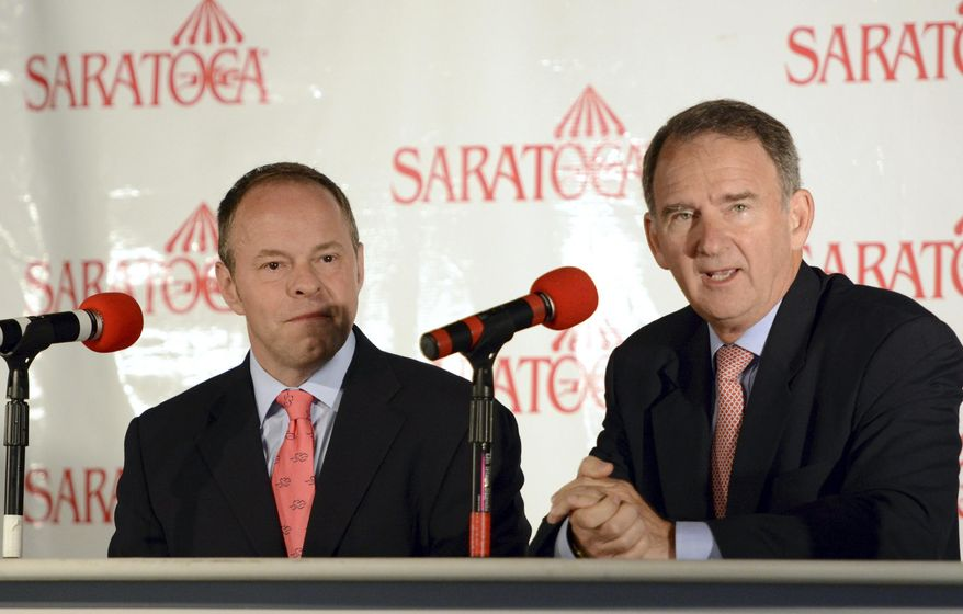 New York Racing Association CEO Christopher Kay, right, addresses the media during a new conference annoucing that Larry Collmus, left, will succeed Tom Durkin as race caller at New Yorks horse racing tracks Wednesday, Aug. 13, 2014, at Saratoga Race Course in Saratoga Springs, N.Y. Durkin is retiring from calling horse races this month at Saratoga after a 43-year career that included announcing the Triple Crown and Breeders' Cup. Collmus was previously the track announcer at Churchill Downs in Louisville., Ky. (AP Photo/The Daily Gazette, Patrick Dodson)  TROY, SCHENECTADY; SARATOGA SPRINGS; ALBANY AND AMSTERDAM OUT