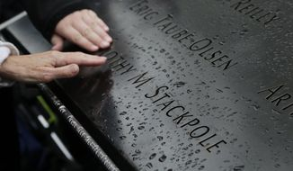 This May 8, 2014, file photo shows people touching the engraved name of a victim of the Sept. 11, 2001, attacks at the National September 11 Memorial & Museum in New York. The memorial has been visited by nearly 15 million people since it opened three years ago on the footprints of the twin towers. (AP Photo/Mark Lennihan, File)