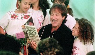 In this April 21, 1996 photo, Robin Williams reads to a group of children during a special children's program at the new main library in San Francisco. Williams helped inaugurate the city's new library by reading stories to the children. Williams was everywhere in San Francisco, it seemed, as he made a place for himself in the everyday fabric of a city where he once said he passed for normal. (AP Photo/San Francisco Examiner, Bob McLeod, File)