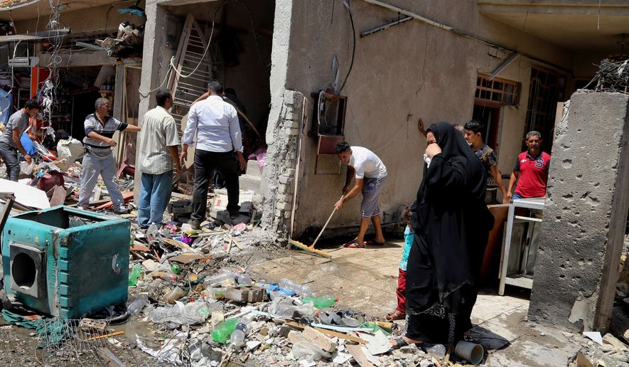 People inspect the site of a car bomb attack as others clear debris in Baghdad, Iraq, Wednesday, Aug. 13, 2014. A string of attacks in and around the capital killed more than a dozen and wounded dozens. (AP Photo/Karim Kadim)