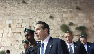 New York Gov. Andrew Cuomo, center, walks at the Western Wall, the holiest site where Jews can pray, during his visit to Jerusalem's old city, Wednesday, Aug. 13, 2014. (AP Photo/Emil Salman)   ISRAEL OUT