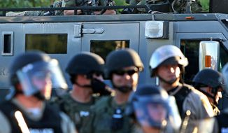 A police sharp shooter keeps an eye on protesters along W. Florissant Avenue on Tuesday, Aug. 12, 2014 near the QuikTrip that was burned down a few days earlier in Ferguson. (AP Photo/St. Louis Post-Dispatch, David Carson)