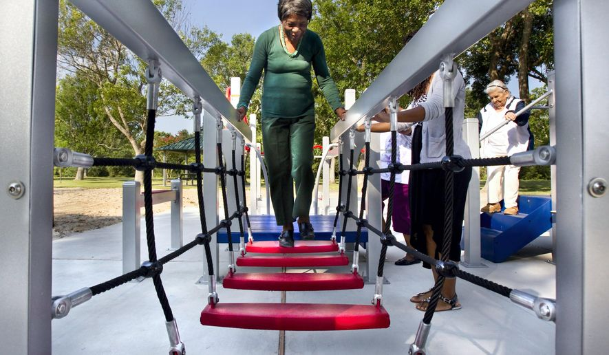 In this photo taken on Wednesday, Aug. 13, 2014, 84-year-old Zady Jones walks across a rope step bridge while trying out the new senior playground at Carbide Park in La Marque, Texas.  The playground will be officially open to the public Thursday, after a ribbon-cutting ceremony. (AP Photo/The Galveston County Daily News, Stuart Villanueva) MANDATORY CREDIT, MAGS OUT, TV OUT