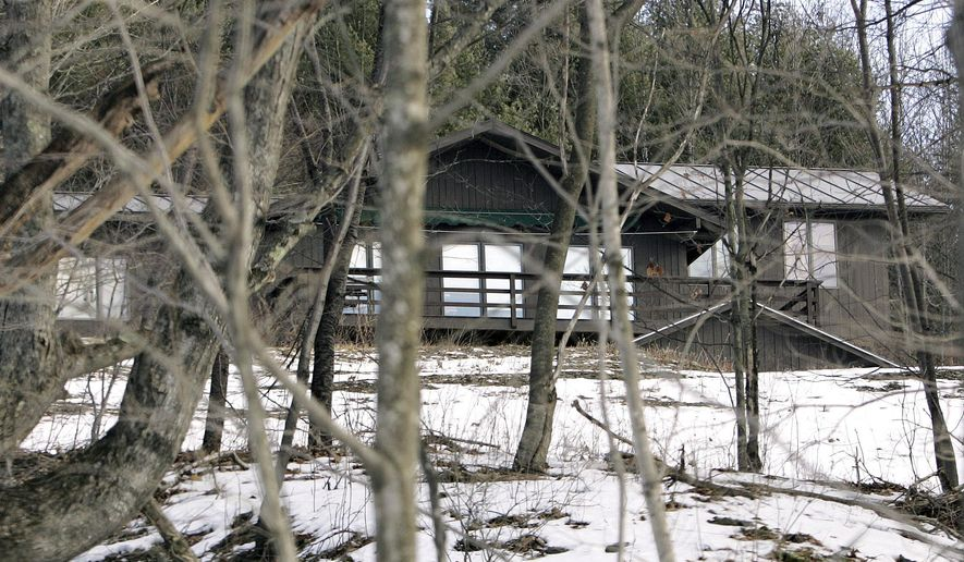 FILE - In this Jan. 31, 2010 file photo, the former home of author J.D. Salinger sits among trees in Cornish, N.H. The home, which Salinger bought in the 1950's, is up for sale again in August 2014. The current owner bought the 2,900-square-foot home on 12 acres in the 1980's. The land once belonged to sculptor Augustus Saint-Gaudens, and a descendant of his built the house in 1939. Salinger left the home after separating from his first wife, but remained in Cornish, where he died in 2010 at age 91. (AP Photo/Jim Cole, File)