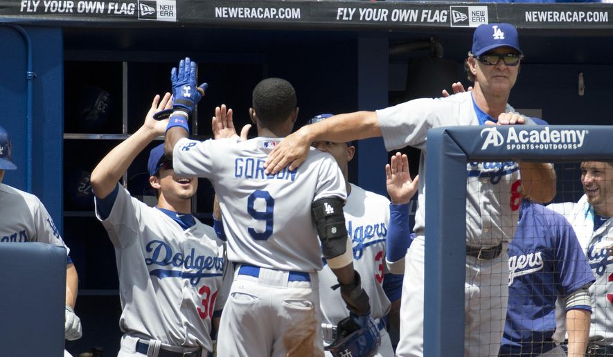 Los Angeles Dodgers second baseman Dee Gordon (9) is greeted at the dugout by manager Don Mattingly (8) and Darwin Barney (30) after scoring on an Adrian Gonzalez base hit in the third inning of a baseball game against the Atlanta Braves Thursday, Aug. 14, 2014, in Atlanta. (AP Photo/John Bazemore)