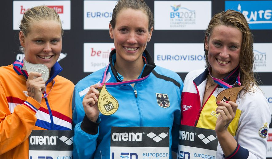 From left, second placed Netherlands' Sharon van Rouwendaal, first placed Germany's Isabelle Haerle and third placed Spain's Mireia Belmonte Garcia show their medals during the medal ceremony of the women's 5km open water swim competition at the LEN Swimming European Championships in Berlin, Germany, Thursday, Aug. 14, 2014. (AP Photo/Gero Breloer)