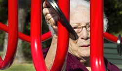 In this photo taken on Wednesday, Aug. 13, 2014, Bertha Pistone, 90, passes a ring across a curved metal structure at an exercise station at the new senior playground at Carbide Park in La Marque, Texas.  The playground will be officially open to the public Thursday, after a ribbon-cutting ceremony. (AP Photo/The Galveston County Daily News, Stuart Villanueva) MANDATORY CREDIT, MAGS OUT, TV OUT