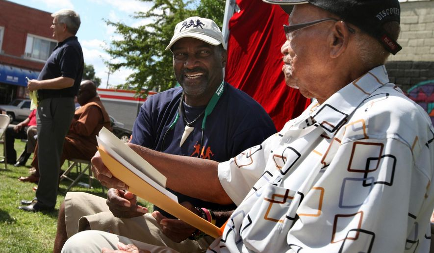 Ike Blessitt, center, a former Detroit Tiger who played in the majors for one year, smiles at Ron Teasley, right, former Negro League baseball player, Wayne State University star athlete and Detroit high school baseball coach after looking at historic photos at a dedication ceremony, Thursday, Aug. 14, 2014 in Hamtramck, Mich. (AP Photo/Detroit Free Press, Jessica J. Trevino)  DETROIT NEWS OUT;  NO SALES; MANDATORY CREDIT