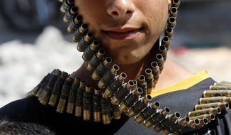 AP10ThingsToSee - A Palestinian youth wraps a bandolier of spent bullets leftover by the Israeli army, next to his destroyed home in Beit Hanoun, Gaza Strip, Monday, Aug. 11, 2014. (AP Photo/Hatem Moussa)
