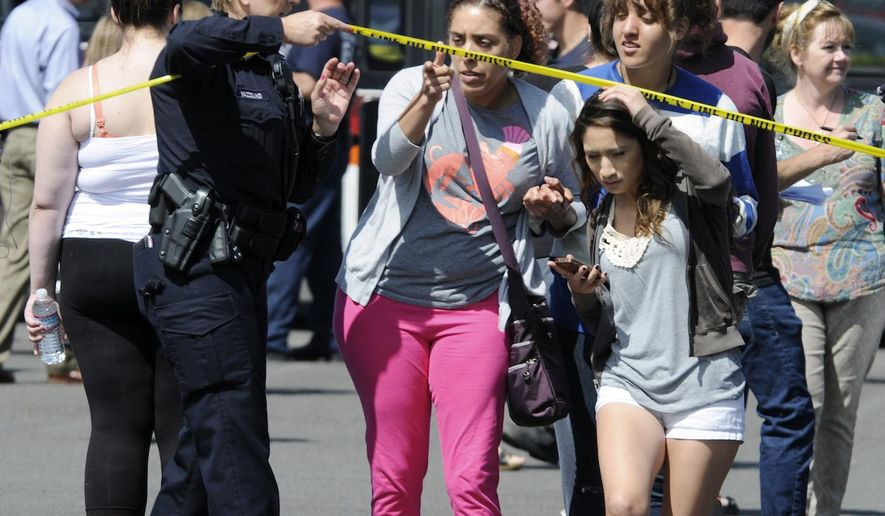 """FILE - In this Tuesday, June 10, 2014, file photo, a police officer lifts up police tape as students arrive by bus to meet their parents and/or family at the Fred Meyer grocery store parking lot in Wood Village, Ore., after a shooting at Reynolds High School, in nearby Troutdale. Police in Washington state are asking the public to stop tweeting during shootings and manhunts to avoid accidentally telling the bad guys what officers are doing. Two recent incidents led the Washington State Patrol to organize the """"TweetSmart"""" campaign: the search for a gunman in Canada after three officers were killed and the shooting at Reynolds High School. (AP Photo/Greg Wahl-Stephens, File)"""