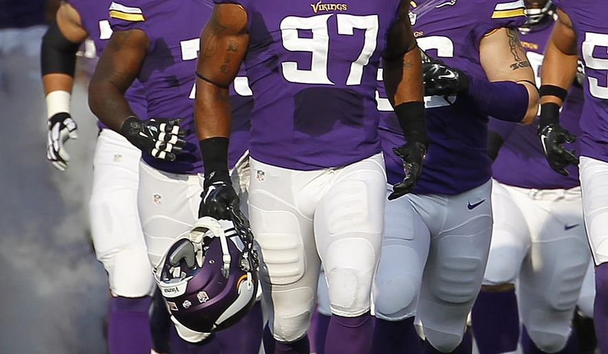 """FILE - In this Aug. 8, 2014 photo, Minnesota Vikings defensive end Everson Griffen (97) leads the team onto the field for a preseason NFL football game against the Oakland Raiders in Minneapolis. Griffen, after two arrests in a three-day period during his rookie year, is what GM Rick Spielman calls """"a success story,"""" a pillar in the community and a leader on the new-look defense. (AP Photo/Ann Heisenfelt,File)"""