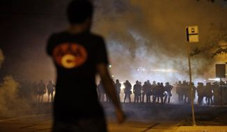 A man watches police through a cloud of smoke in Ferguson, Mo., the St. Louis suburb rocked by racial unrest after a white police officer shot an unarmed black teenager to death. (AP Photo/Jeff Roberson)