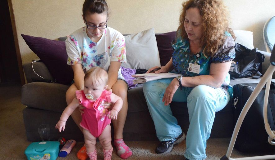 ADVANCE FOR SUNDAY, AUG. 17 - In this photo taken on Aug. 1, 2014, Elizabeth Markham, holding daughter Roann, who was born in February, meets with nurse Heidi Pengra, of the Nurse and Family Partnership, during a recent home visit in Battle Creek, Mich. The NFP is a nationwide program that connects nurses to clients at or near the beginning of their pregnancy. Those nurses then continue to meet with the client and her family throughout pregnancy, childbirth and until the child is two years old. (AP Photo/Battle Creek Enquirer, John Grap)