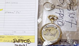 ADVANCE FOR SUNDAY, AUG. 17 - A watch and rings sit in an evidence property bag at the Dallas Police Department's property room on Baylor Street in Dallas on Tuesday, Aug. 5, 2014. (AP Photo/The Dallas Morning News, Andy Jacobsohn)