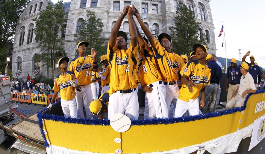 Members of the Jackie Robinson West Little League team from Chicago, Ill., ride in the Little League Grand Slam Parade as it makes its way through downtown Williamsport, Pa., Wednesday, Aug. 13, 2014. The Little League World Series tournament begins Thursday, August 14, in South Williamsport, Pa.  (AP Photo/Gene J. Puskar)
